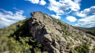 Timelapse White clouds move across bright blue skies casting shadows over barren desolate Grampians rockface and bushland