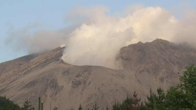 Timelapse wide shot of steam erupting from volcanic crater in dawn light, Japan