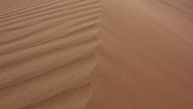 Timelapse wind blows sand from crest of sand dune in desert, UAE