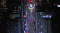 AERIAL Times Square amongst the buildings of New York City, lit up at night, and traffic driving on streets / New York, United States
