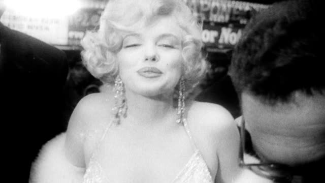 Times Square at night / fans holding up photograph of Marilyn Monroe / Marilyn and husband Arthur Miller arrive at premiere of her new film Some Like...