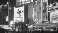 1949 MONTAGE Times Square at night in New York City, with flashing neon signs and pedestrian and vehicle traffic / New York, United States