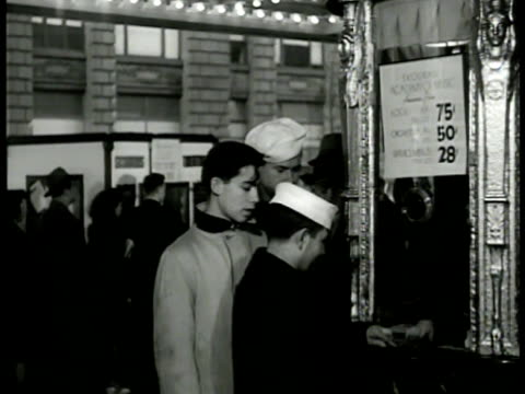 Times Square w/ minimal lighting US Sailor buying ticket at Skouras Academy of Music w/ others CU Posted ticket prices 75 cents 50 cents 28 cents Man...