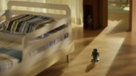 Tin robot toy walking on parquet floor in kids room