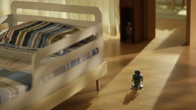 Tin robot toy walking on parquet floor in kids room