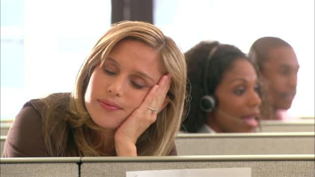 CU, Tired female customer service representative resting in office cubicle