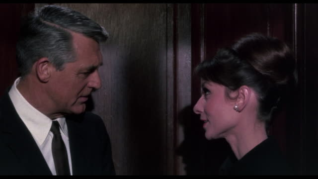 Tired man (Cary Grant) escorts flirting woman (Audrey Hepburn) from elevator to hotel room