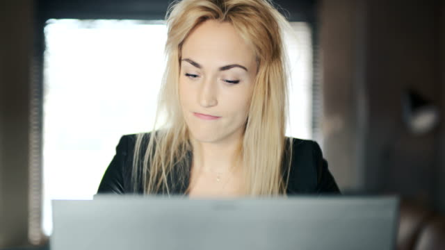 Tired Young Businesswoman Using Laptop In Office
