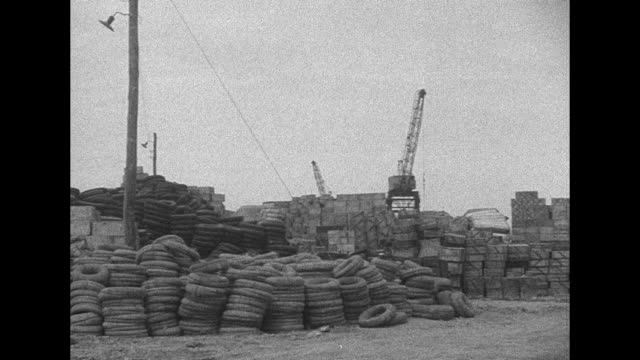 MSPAN tires and boxes stacked up in train yard derrick cranes in background / LS train chugs into distance issuing smoke from smokestack mountains in...