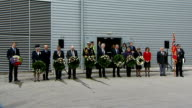 Ceremony held in Southampton People holding wreaths for minute silence / ships horns SOT / ships pulling out of harbour