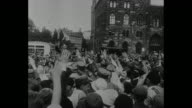 Title '1929' superimposed on Brown Shirts marching as they approach pass camera while saluting / Adolf Hitler rides through crowd in car / spectators...