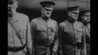 'Arrived' / US Gen John J Pershing stands with other officers at side of train car French Gen Etienne Pelletier at left