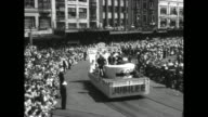 Title 'Australia Marks 50 Years as a Unified State' superimposed over WS parade along crowded city street / VS high and street shots of parade with...