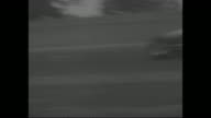 Title 'Auto Racing' superimposed over racetrack at Indianapolis 500 / various shots cars racing one driven by Bill Vukovich / multiplecar crash...
