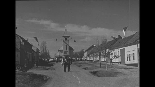 'Bltanicka' [sic] superimposed over shot of village street and Church of the Assumption at end of street / overhead view of girls dressed in...