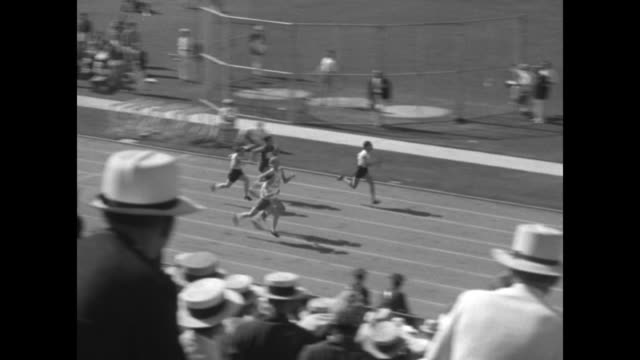 '100 Meter Dash Trials Women' / 8/1/1932 Spectators rise in foreground as racers take off from starting line during heats of 100m dash / race ends /...