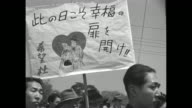 '3000 Japanese Hold A Picnic Object Matrimony' / two shots of crowd male members of 'Hope' club walking past camera / crowd of female members of club...