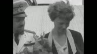 'Amelia Earhart Putnam is welcomed to Rome by Italian Minister of Air General Balbo' / Earhart with flowers General Italo Balbo Earhart and others...