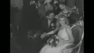 'Anita Ekberg Anthony Steel Wed in Italy' superimposed over actor Anthony Steel and actress Anita Ekberg amidst a crowd of people at City Hall in...