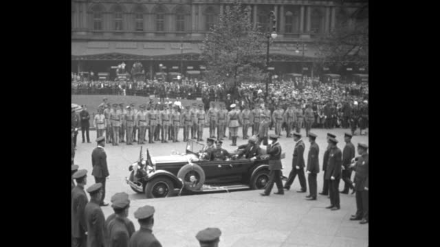 'Arriving at City Hall' / limousine with Police Commissioner Grover Whalen and Hugo Eckener comes to a stop with line of police beyond / title 'With...