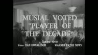 'Baseball News' superimposed over players in stands with bats / Title card 'Musial Voted 'Player Of The Decade'' superimposed over interior of...