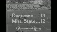 ''Bowlsfull' of football thrill nation' / title 'Duquesne 13 Miss State 12' superimposed on game in progress / VS game in progress