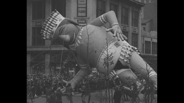 'Christmas Draws Near East and West' / title 'New York' superimposed over balloon of Native American in Macy's Thanksgiving Day parade in Manhattan /...