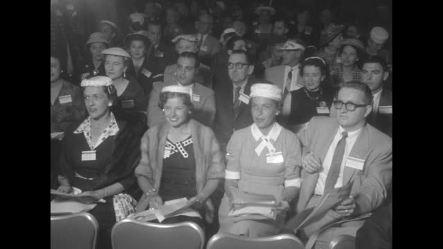 ''Citizens for Ike' kick off their campaign' superimposed over people seated in audience / shot of audience looking forward / large poster with photo...
