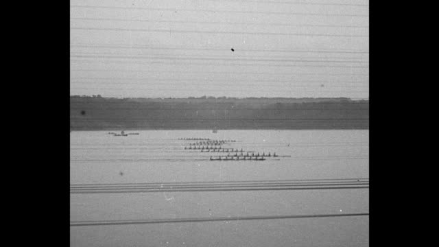 'Columbia wins from 8 crews Poughkeepsie NY Big crowds watch shells in Intercollegiate Regatta' / POV shells far away on Hudson River with telephone...