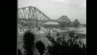 'Decorate Biggest Span In Scotland Firth of Forth Daring workmen paint giant arches of noted cantilever bridge 1710 feet long' / WS railroad bridge...