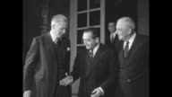 'Dulles Back After Quick Paris Parley' superimposed over John Foster Dulles walking with others / French Prime Minister Pierre Mendes France and...