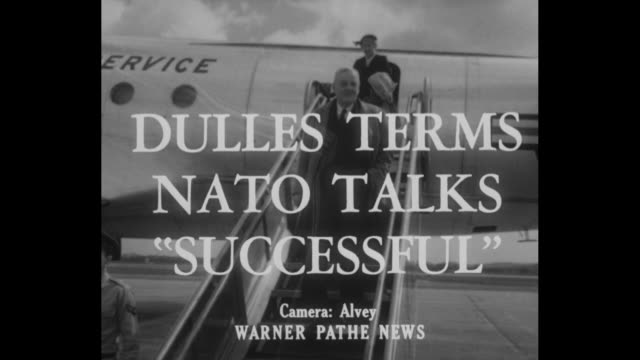 Title card 'Dulles Terms NATO Talks Successful' / CU Secretary of State John Foster Dulles walks across tarmac shakes hands with Italian ambassador...