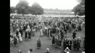 Title card 'Elizabeth's Horse Wins at Ascot' / Tilt down large crowd of people milling about on grounds / Tilt down Queen Elizabeth Philip and the...