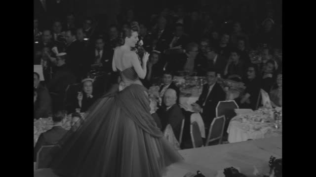 'Fashion Show for March of Dimes' superimposed over WS crowd in attendance / actress Grace Kelly and March of Dimes poster girl Mary Kosloski examine...