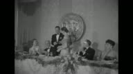 'Film Stars get Photoplay Awards' superimposed over ceremony attendees seated at round tables in the Statler Hilton in Los Angeles for the Photoplay...