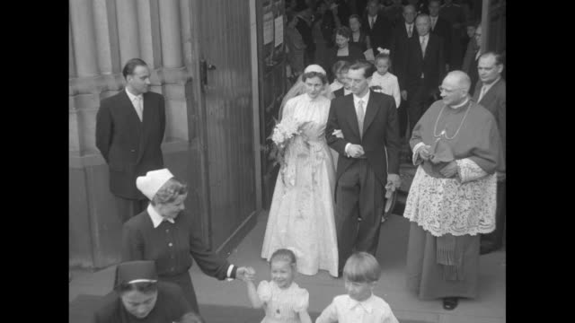 'First Lady of Germany 29 is Wed' superimposed over German Chancellor Konrad Adenauer in formalwear walking with his daughter Lotte Adenauer down...