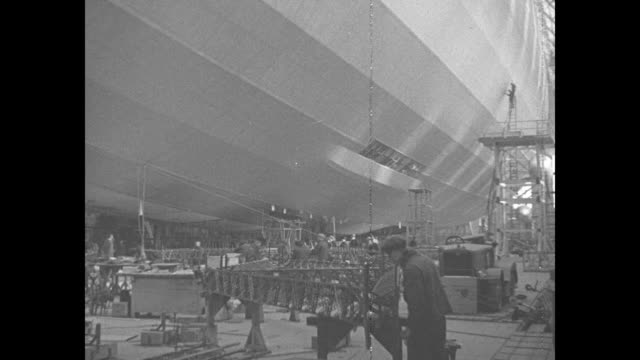 'Germany's New Zeppelin Ready' / montage Hindenburg dirigible in hangar in Friedrichshafen Germany with workers and scaffolding nearby / worker...