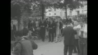 'Grace Rainier Visit Paris' superimposed over Rainier and Grace exiting a building / MS Prince Rainier III and Princess Grace Kelly on terrace / WS...