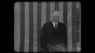 'Hoover Attacks New Deal Former President opens '36 campaign at Oakland Banquet of Young Republicans' / WS of Hoover speaking large US flag hanging...