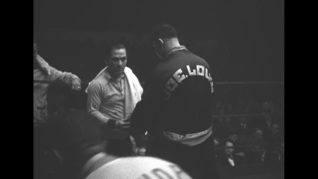 'Louis Beats Foxworth in Chicago Bout' /MS Louis wearing robe and towel draped over his head steps up to ropes on outside of ring / WS Louis steps...