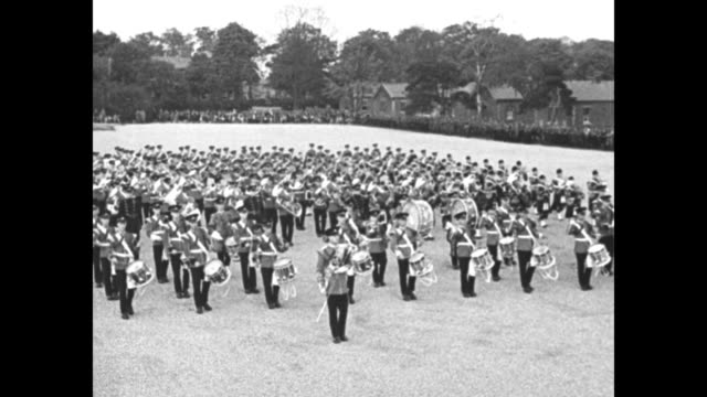 'Massed Bands Rehearse For Aldershot Tattoo' / bagpipe band in full costume marching drum major in front drum major reverses direction and members...