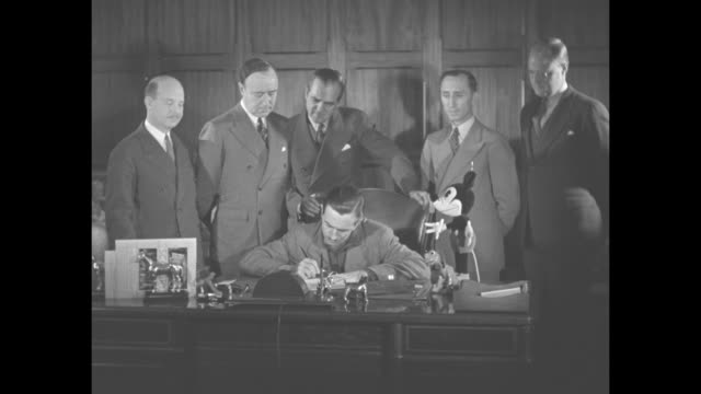 'Mickey Mouse Signs Up' superimposed over Disney company executive Walt Disney holding up a Mickey Mouse stuffed toy and SOT speaks in the...