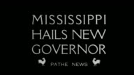 'Mississippi Hails New Governor'/ shot of exterior of state Capitol decorated with bunting tilt down to people gathered on platform also decorated...
