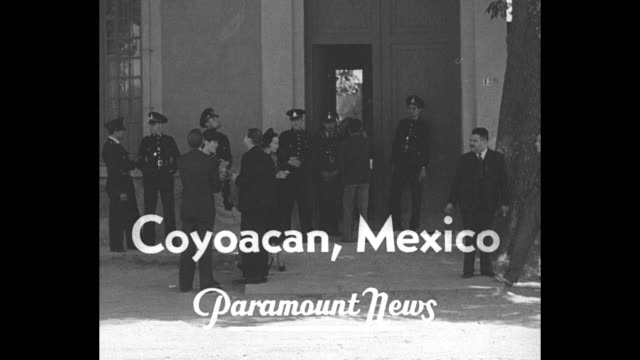 'News Flashes from Everywhere' / title 'Coyoacan Mexico' over police guarding the home of Diego Rivera and his wife Frida Kahlo / CU Kahlo / John...