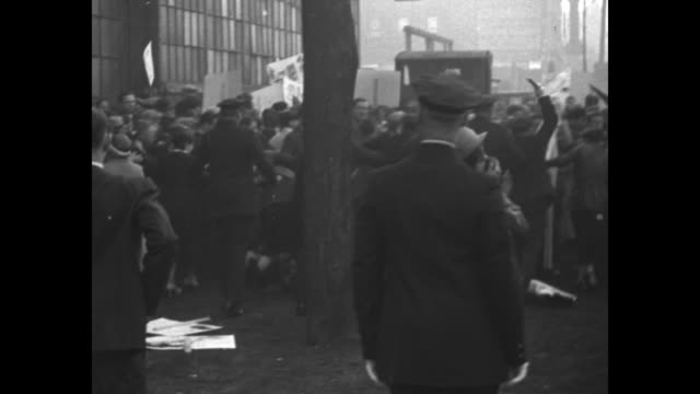 'News Flashes' / police clashing with crowd can see police raising nightsticks woman falls to ground / crowd in street by building police on...