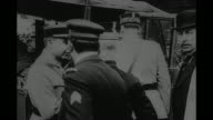 'Off for his train to Paris' / US Gen John Pershing stands with French Gen Etienne Pelletier as Pershing enters rear of automobile which then drives...