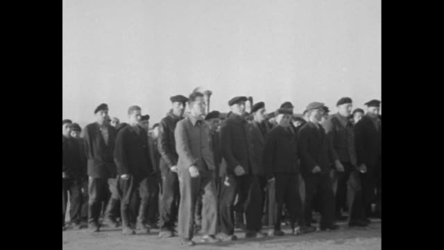 'Official US Army Signal Corps Motion Pictures' / crowd of prisoners gathered in front of camp some holding flags / two shots of band composed of...