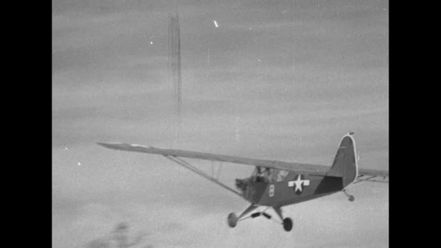'Pacific Grasshopper Planes on Bougainville Is' / CU grasshopper insignia on side of Piper J3 observation airplane / MS mechanic kicks front of plane...