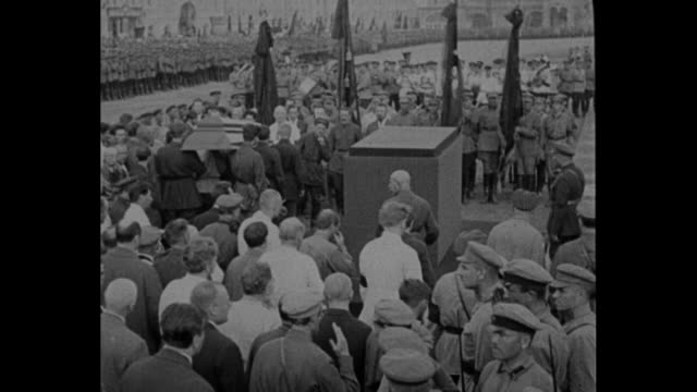 'Premier Alexis Rykoff Leads Cortege to Catafalque in the Great Red Square and Leo Trotsky Walks Beside the Casket' / Tilt down huge procession led...