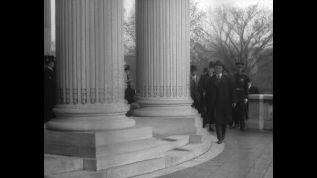 / Pres Woodrow Wilson walking past pillars of US Capitol with group of officials and officers / Note film has nitrate deterioration
